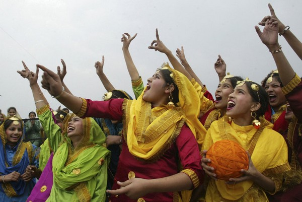 School girls wearing colourful dresses cheer as they fly a kite during an event to mark the Basant or spring festival in Amritsar