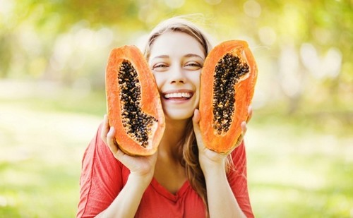 woman holding two papaya halves smiling